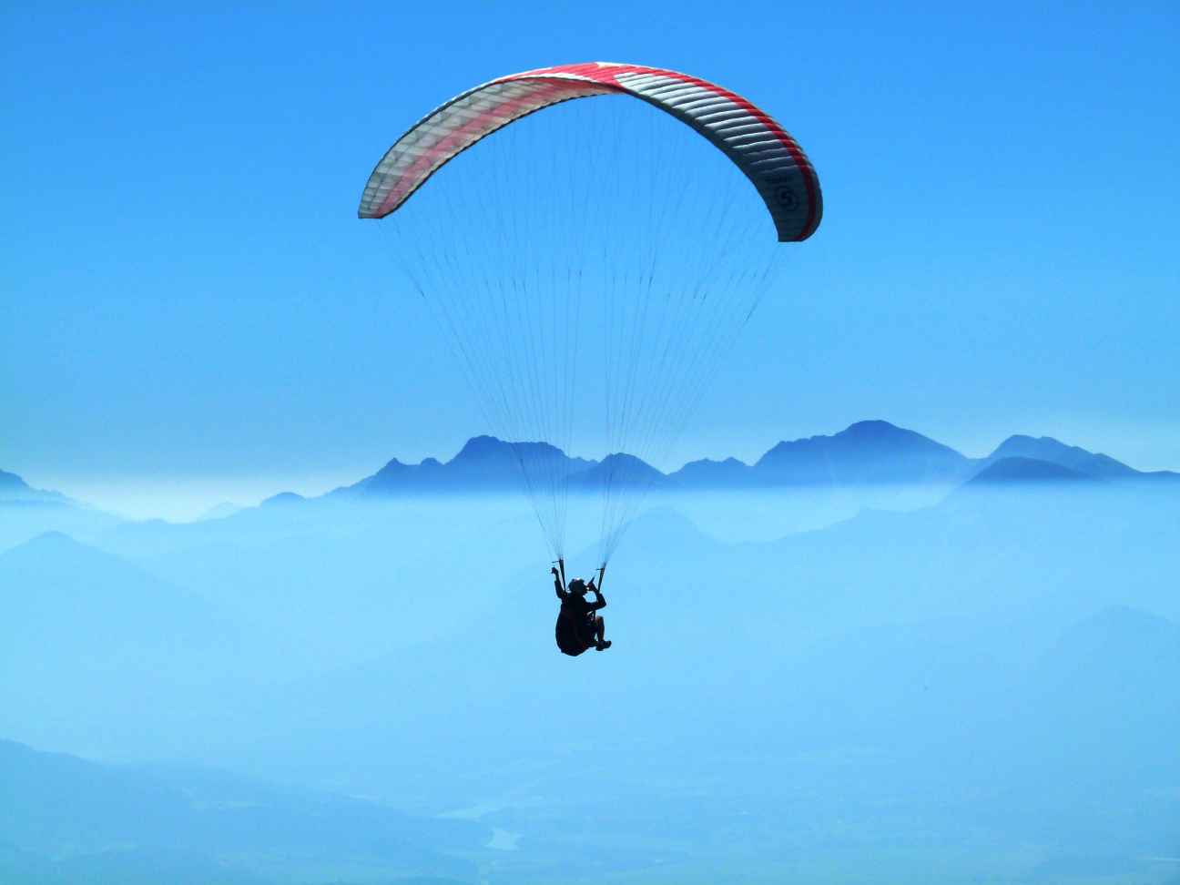 person-doing-paragliding-above-clouds-during-daytime-65677